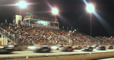 The NASCAR K&N Pro East Series cars zip past a packed main grandstand of the rain-delayed race. (Mike Lysakowski/ Motorsport Aspects)