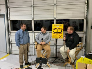 "Host Charles Head (right) and his first producer Dave Sherman (left) chat with dirt Late Model driver Kenny Collins. ""Super Dave"" competed in sportsman races at Lanier for several years. (The yellow sign is backwards here so it could show up on Facebook Live."